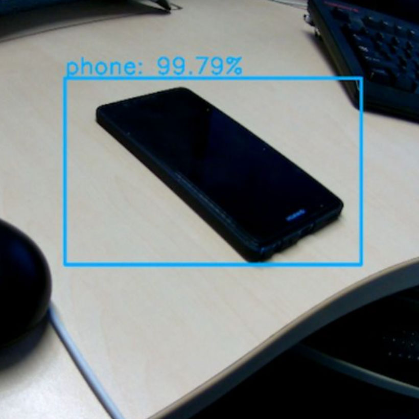 Phone on table highlighted with blue bounding box with a confidence score of 99.79%
